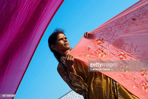 Woman pilgrim dries a saree after the holy dip at the confluence of the rivers Ganges and Yamuna during Maha Kumbh mela. Kumbh Mela is a site of mass...