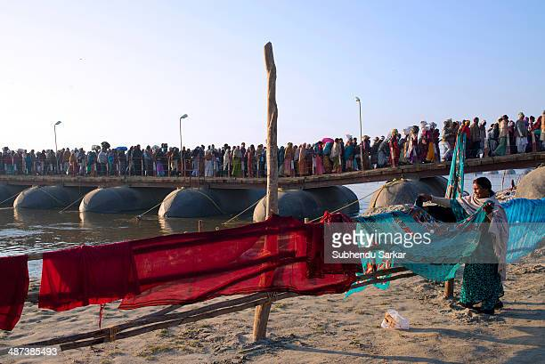Woman pilgrim dries sarees after the holy dip near the pontoon bridges during Maha Kumbh mela. Kumbh Mela is a site of mass pilgrimage in which...