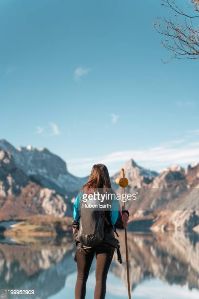 woman pilgrim on the way to santiago de compostela looking at the landscape and mountains - cammino di santiago di compostella foto e immagini stock