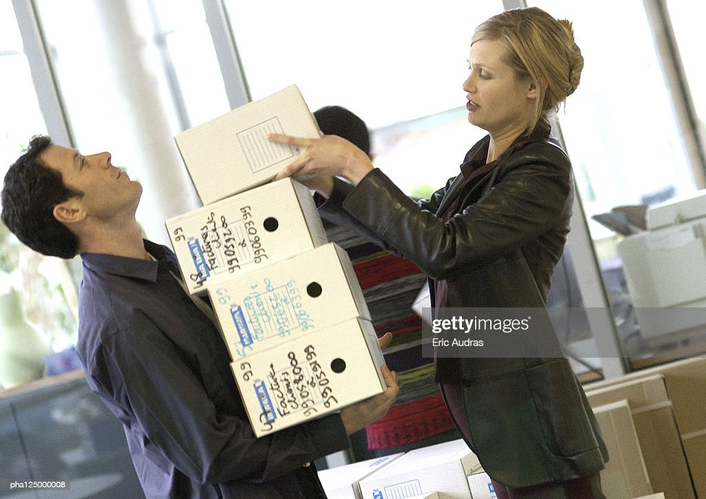 Woman piling boxes up on man's arms, side view : Stockfoto