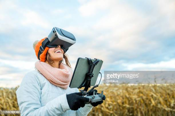 woman pilot using drone remote controller with a tablet mount and virtual reality goggles - remote controlled stock photos and pictures