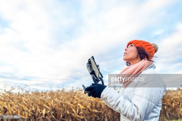 woman pilot using drone remote controller with a tablet mount - remote controlled stock photos and pictures