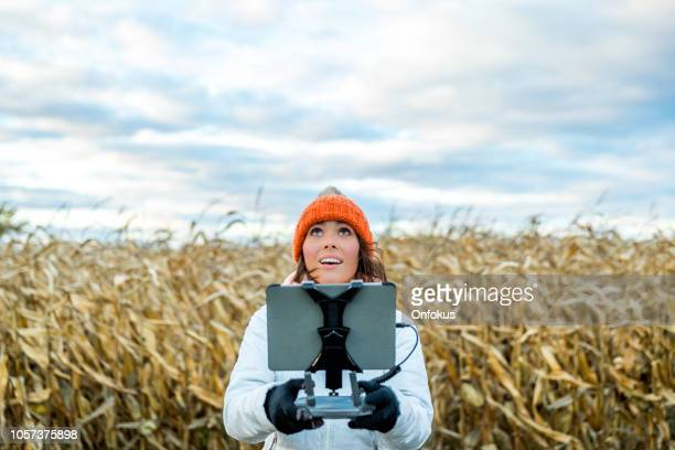 woman pilot using drone remote controller with a tablet mount - drone stock pictures, royalty-free photos & images