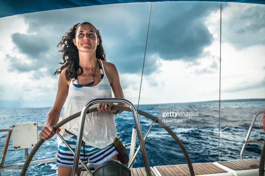 Woman piloting a sailboat : Stock Photo