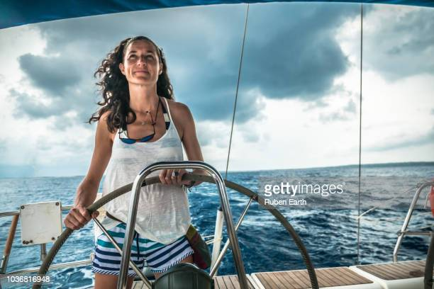 woman piloting a sailboat - team captain stock pictures, royalty-free photos & images