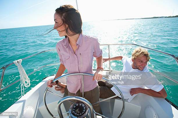 A woman pilots a boat off of Florida while a man sits nearby.