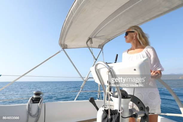 woman pilots sailing yacht, on open sea - yachting stock pictures, royalty-free photos & images