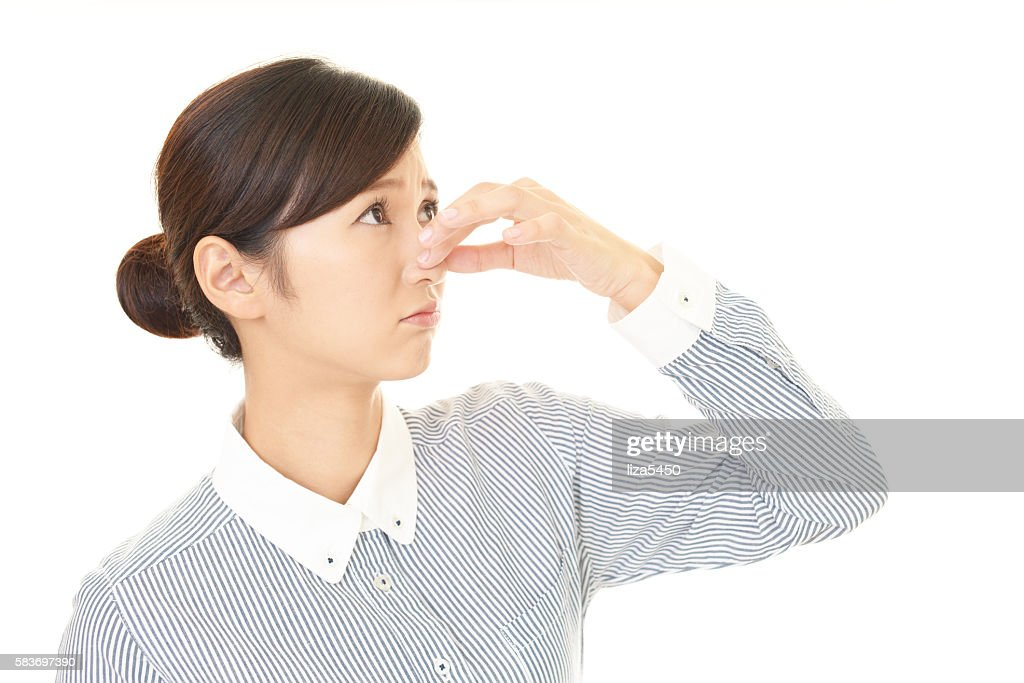 Woman pinches her nose : Stock Photo