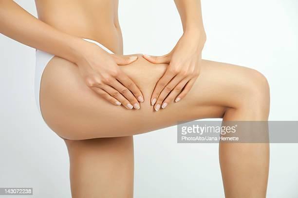 Woman pinching body fat on leg, cropped