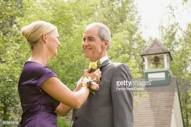 Woman pinning boutonniere on husband