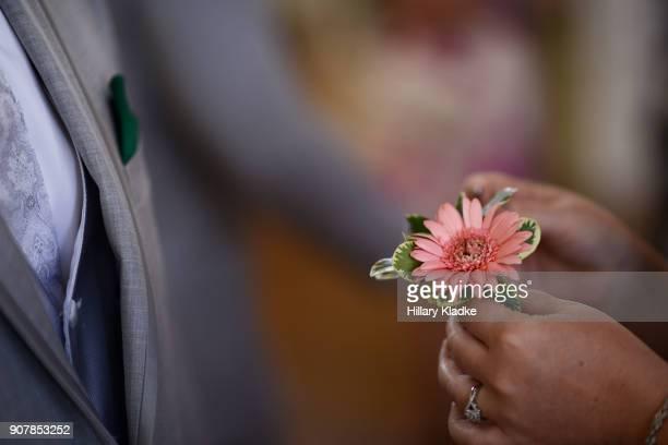 Woman pinning corsage on Groom