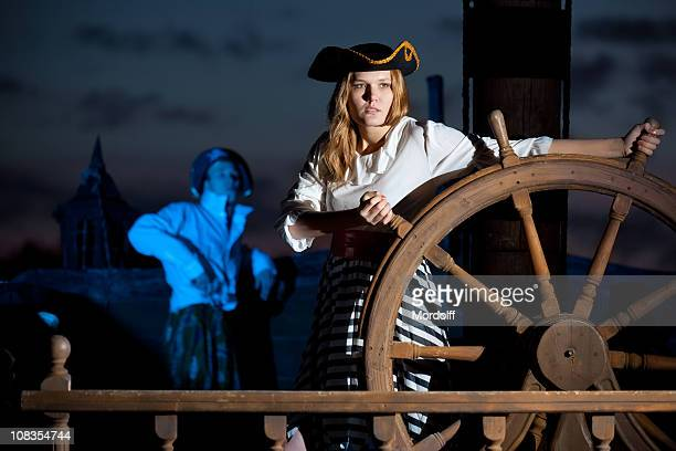 woman pirate at captain's wheel - female pirate stock photos and pictures