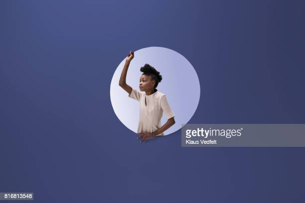 Woman placed inside round opening in coloured wall