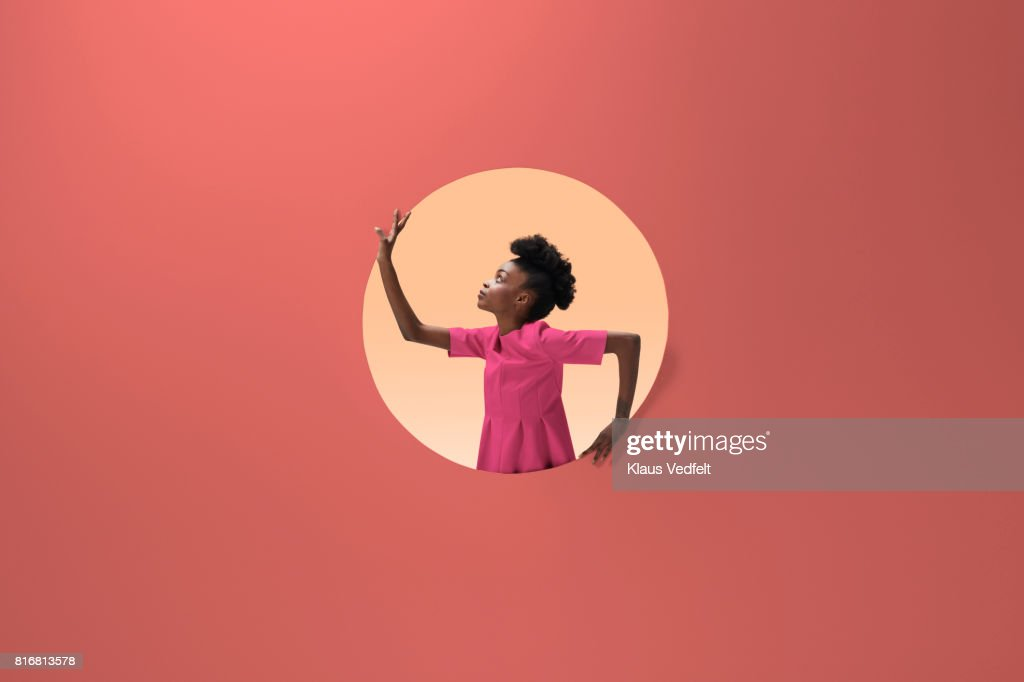 Woman placed inside round opening in coloured wall : Stock Photo
