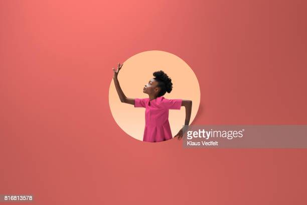 woman placed inside round opening in coloured wall - couleur corail photos et images de collection