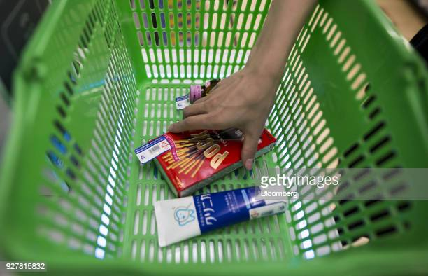 A woman places a basket of items with radiofrequency identification tags on an unmanned cash register during a demonstration at a FamilyMart UNY...