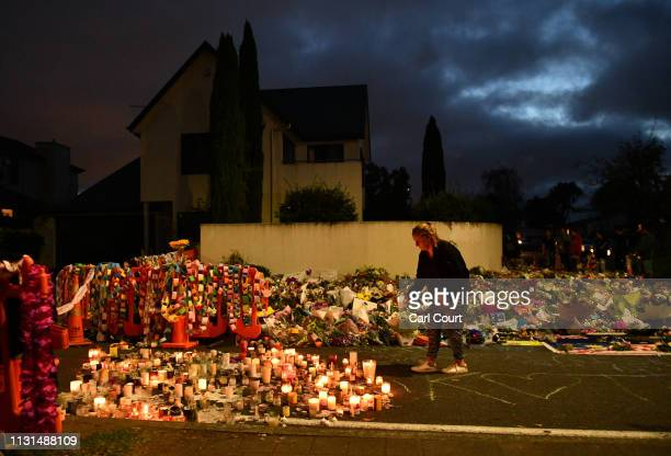 A woman places a candle amongst flowers and tributes near Al Noor mosque on March 19 2019 in Christchurch New Zealand 50 people were killed and...