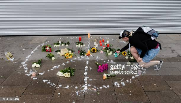 TOPSHOT A woman places a candle at a makeshift memorial of flowers and candles arranged like a peace sign on July 29 2017 in Hamburg northern Germany...