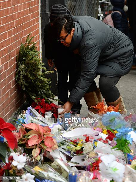 A woman places a candle at a memorial near Tompkins Ave and Myrtle Ave December 21 2014 in New York near the site where two New York City police...