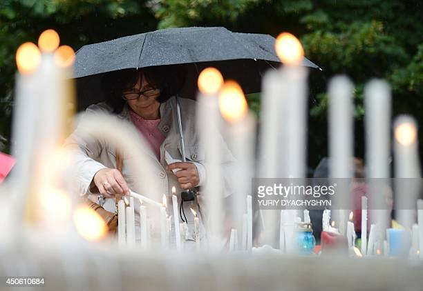 A woman places a candle during a memorial ceremony for the people killed when a Ukrainian military plane was shot by proRussian armed separatist...