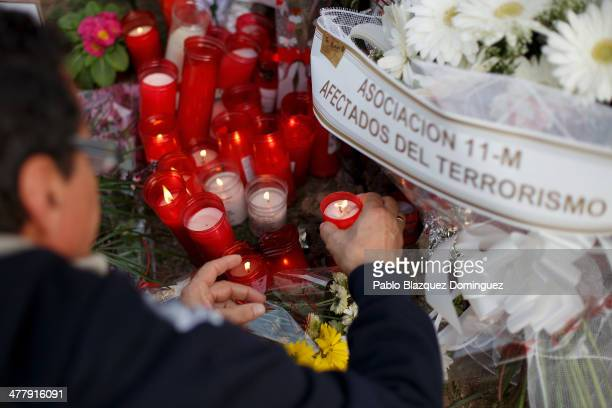 A woman places a candle for the victims of Madrid train bombings at a memorial monument at Santa Eugenia train station during the 10th anniversary on...