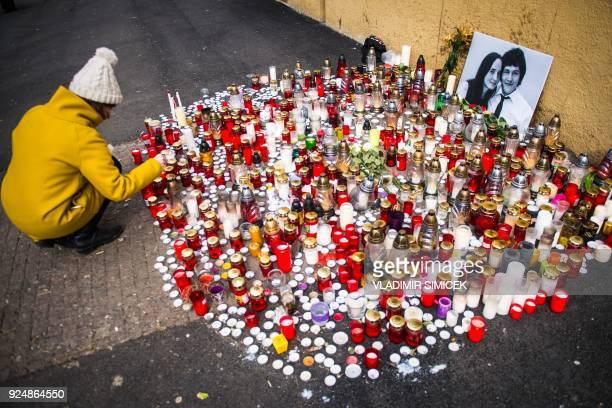 A woman places a candle in front of a portrait of Slovak investigative journalist Jan Kuciak and his girlfriend Martina Kusnirova in the center of...