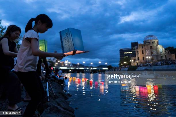 A woman places a candle lit paper lantern on the river during an event to commemorate the 74th anniversary of the atomic bombing of Hiroshima at the...