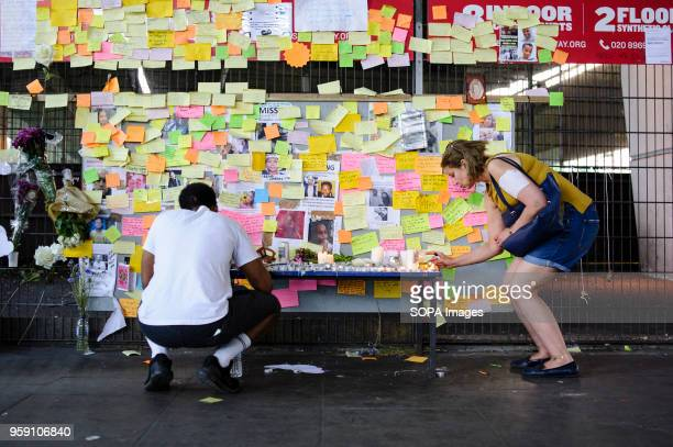 A woman places a candle on a makeshift shrine near the blackened shell of 24storey residential block Grenfell Tower in North Kensington west London...