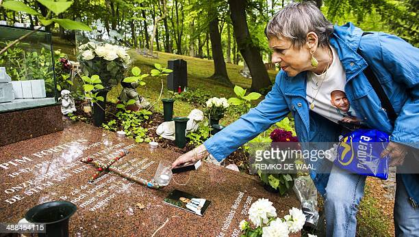 A woman places a candle on May 6 2014 in Driehuis on the grave of slain farright Dutch politician Pim Fortuyn in his remembrance 12 years after he...