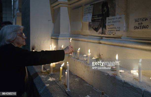 A woman places a candle outside the judicial morgue where an autopsy of the corpse of Santiago Maldonado disappeared on August 1st during a Mapuche...