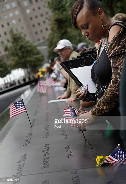 A woman places a flag on a name on the 9/11 Memorial during the tenth anniversary of the September 11 2001 terrorist attacks at the World Trade...