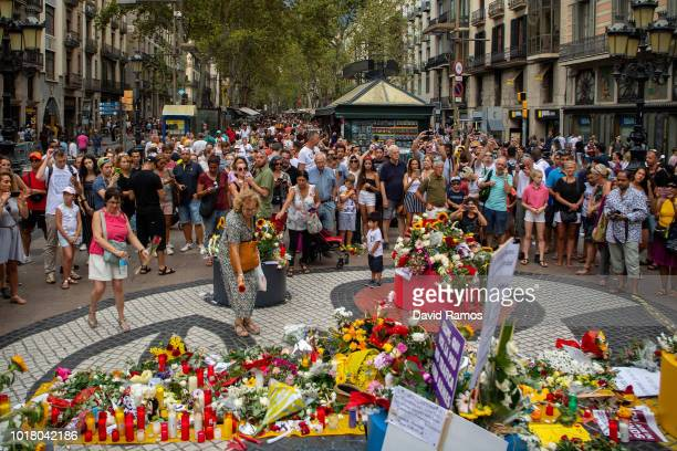 A woman places a flowers in a floral tribute at Las Ramblas on August 17 2018 in Barcelona Spain The Barcelona City Council organized a ceremony in...