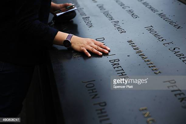 A woman places a hand on the names engraved along the South reflecting pool at the Ground Zero memorial site during the dedication ceremony of the...