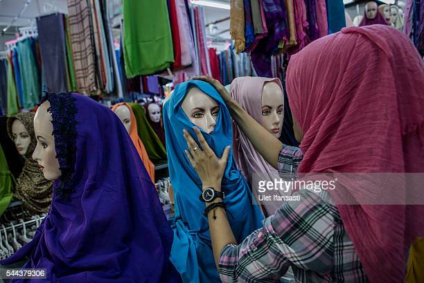 A woman places a headscarf on a mannequin for display at a hijab shop in preparation for Eid AlFitr on July 3 2016 in Yogyakarta Indonesia Eid AlFitr...