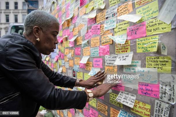A woman places a message next to other notes on a plinth on London Bridge following Saturday's terror attack on June 8 2017 in London England Eight...