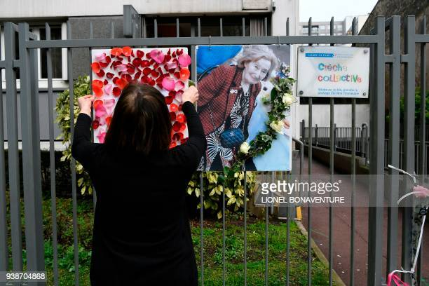 A woman places a picture and tributes to Mireille Knoll on the fence surrounding her building in Paris on March 27 after she was found dead in her...
