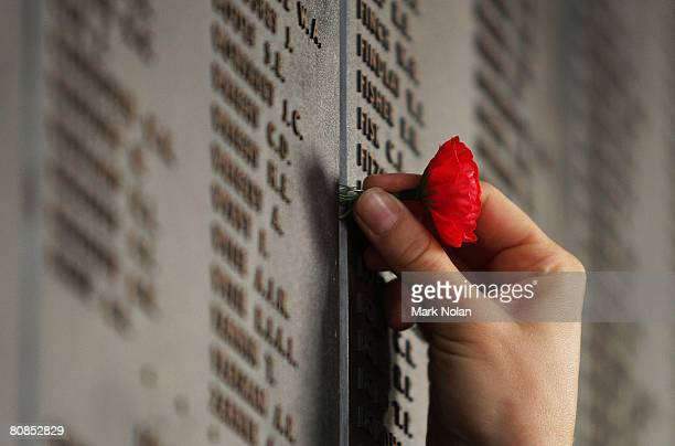 A woman places a poppy on the Roll of Honour for World War I after the ANZAC Day Dawn Service at the Australian War Memorial on April 25 2008 in...