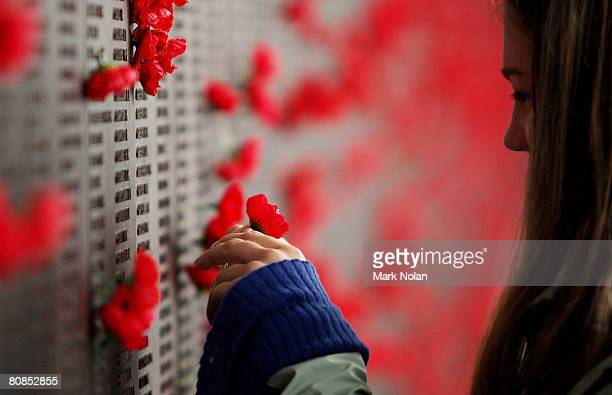 Woman places a poppy on the Roll of Honour for World War I after the ANZAC Day Dawn Service at the Australian War Memorial on April 25, 2008 in...