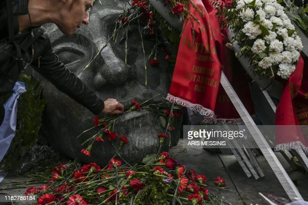 A woman places a red carnations on the monument in memory of the victims of the 1973 student's uprising against the USbacked military junta at the...