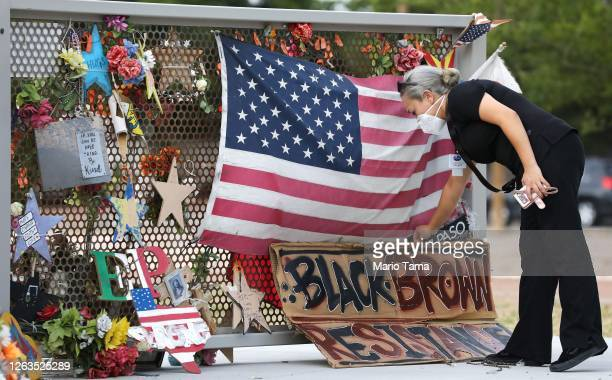 Woman places a sign at a temporary memorial in Ponder Park honoring victims of the Walmart shooting which left 23 people dead in a racist attack...