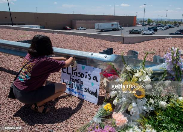 A woman places a Stay Strong sign beside a makeshift memorial outside the Cielo Vista Mall WalMart where a shooting left 20 people dead in El Paso...