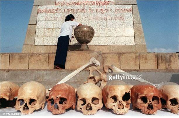 A woman places an offering into an urn behind a row of human skulls during Day of Hate ceremonies in this file photop dated 22 May 1992 marking the...