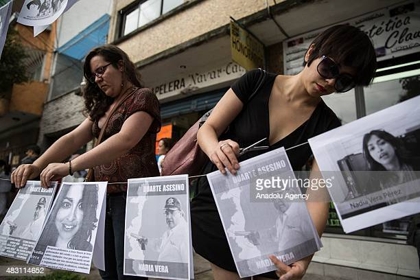 A woman places banners during a protest outside the apartment where the murder of Ruben Espinosa took place to demand justice and the clarification...