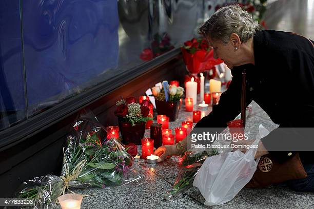 A woman places candles and flowers for the victims of Madrid train bombings outside a memorial monument at Atocha railway station during the 10th...