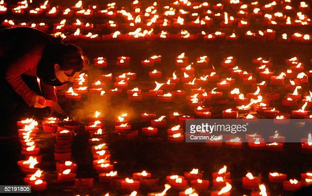A woman places candles in the old marketplace to commemorate victims of WW II on February 13 2005 in Dresden eastern Germany 60 years ago on February...
