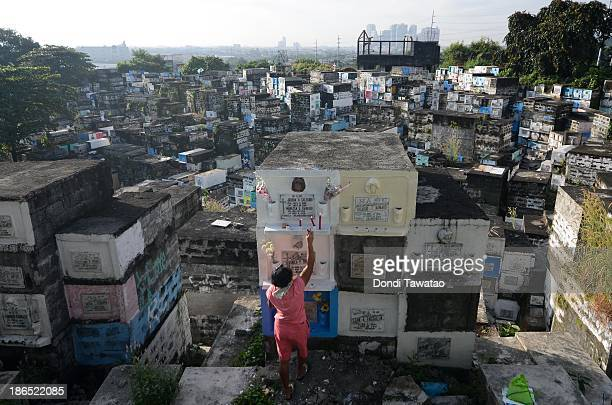 CITY PHILIPPINES A woman places candles on a tombstone at a public cemetery carved into the side of a mountain as All Saints' Day is celebrated on...