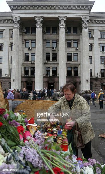 Woman places candles outside the burnt Trade Union building in memory of people killed in recent clashes in the South-Ukrainian city of Odessa,...