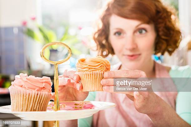Woman places cupcake on cake plate.