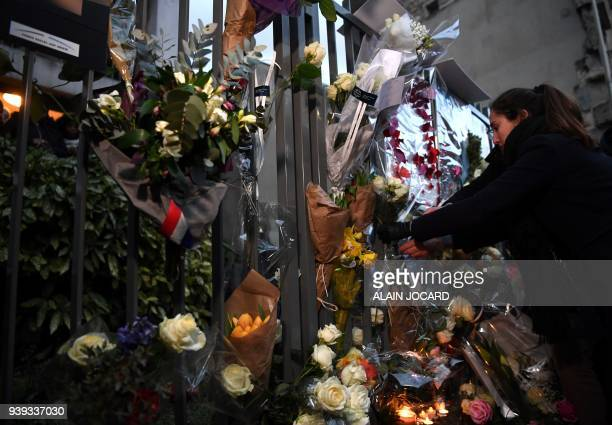 A woman places flowers as he gathers with others at the entrance to an apartment building in Paris on March 28 at the conclusion of a march in memory...