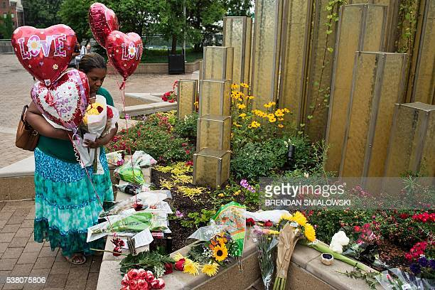 A woman places flowers as she pay respects at a makeshift memorial for boxing legend Muhammad Ali at the Muhammad Ali Center on June 4 2016 in...